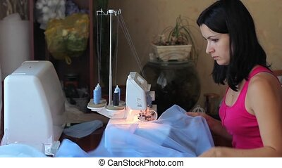 Beautiful woman sews. Raises cloth on the table. Powered by overlock. Work is fun. Favourite buisness.