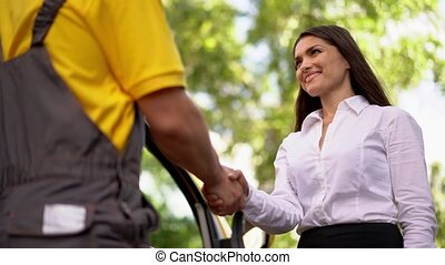 Beautiful woman shakes hands with a courier outside -...