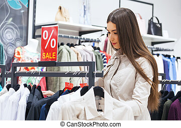 Beautiful woman shopping and looking at some clothing. -...