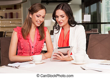 Beautiful woman showing her friend photos on ipad. Sharing...