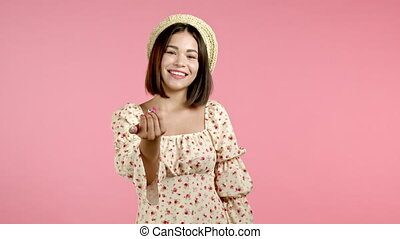 Beautiful woman showing - Hey you, come here. Girl in floral dress ask join her, beckons with inviting hand hugs gesture. Lady is looking playful flirtatious, inviting to come. Pink studio background