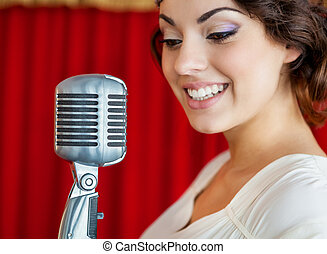 Beautiful woman singing with the microphone