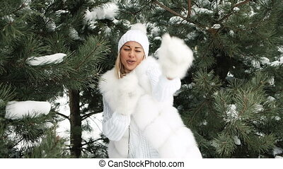 Beautiful woman sings and dances against background of winter landscape.