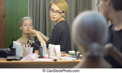 Beautiful woman sits in front of mirror in dressing room.