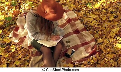 Beautiful woman sits on a plaid in the autumn forest, makes...
