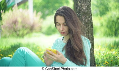 Beautiful woman sits under a tree with a smartphone in a summer park