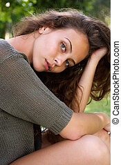 Beautiful woman sitting and leaning over with hand in hair
