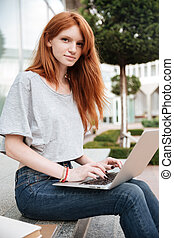 Beautiful woman sitting and using laptop outdoors