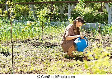 Beautiful woman sitting and watering the plants