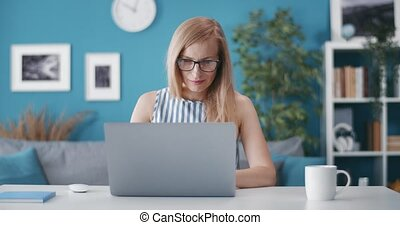 Beautiful woman sitting at home office and working on laptop...
