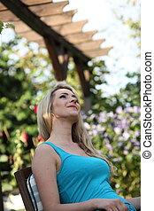 Beautiful woman sitting daydreaming