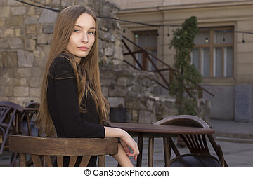 Beautiful woman sitting in a street cafe