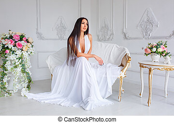 beautiful woman sitting in a white dress on a chair