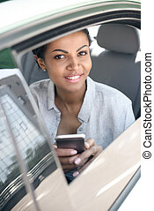 Beautiful woman sitting in car with smartphone and smiling at camera
