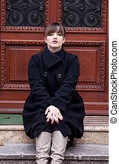 Beautiful woman sitting in front of doorway