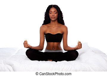 Beautiful woman sitting in lotus yoga pose on bed
