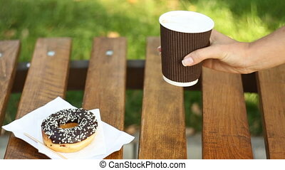 beautiful woman sitting on a bench in the park and eating a muffin and a latte