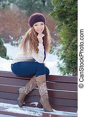 beautiful woman sitting on a bench