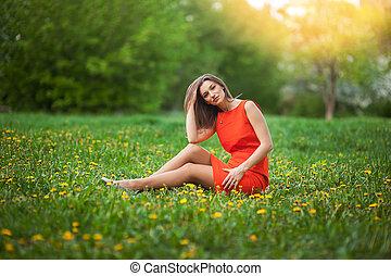 beautiful woman sitting on a field