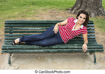 beautiful woman sitting on a park bench