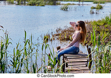 Beautiful woman sitting on a pier at the lake