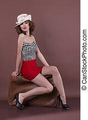 beautiful woman sitting on a retro suitcase