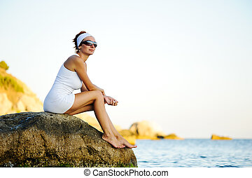 woman sitting on a stone in the sea