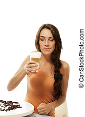 beautiful woman sitting on a table looking at the latte macchiato coffee in her hand on white background