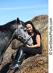 Beautiful woman sitting on hay bale and gray horse - ...