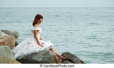 Beautiful Woman Sitting On Rock By Sea