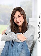 Beautiful woman sitting on sofa at home