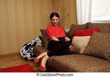 Beautiful woman sitting on sofa