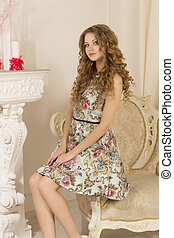 Beautiful woman sitting on the armchair