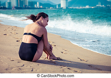 Beautiful woman sitting on the beach in black swimsuit enjoying summer holidays looking at the sea.