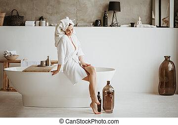 Beautiful woman sitting on the edge of bathtub.