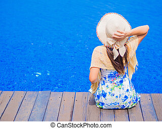 Beautiful woman sitting on the edge of the swimming pool.