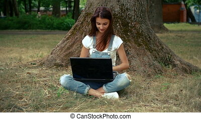 beautiful woman sitting on the grass near the tree with a laptop