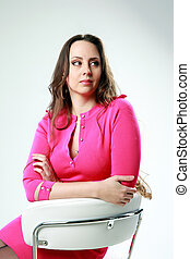 Beautiful woman sitting on the office chair on gray background