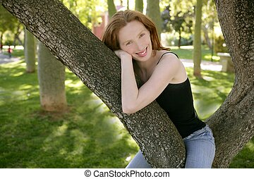 Beautiful woman sitting on the park tree