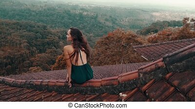 Beautiful woman sitting on the red house rooftop - Aerial...