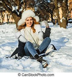Beautiful woman sitting on winter snow outdoor