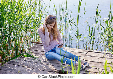 beautiful woman sitting on wooden pier the river