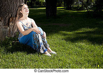 beautiful woman sitting under a tree in park