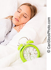 Beautiful woman sleeping with alarmclock on the bed