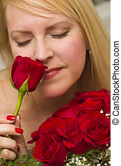Woman Smelling a Bunch of Red Roses
