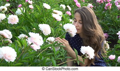 beautiful woman smelling a white peony flowers in the summer garden