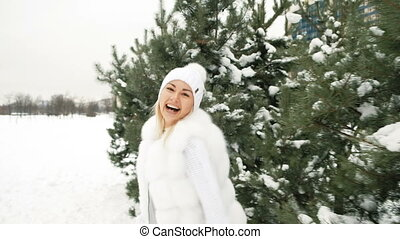 Beautiful woman smiles against background of coniferous trees.