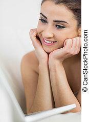 Beautiful woman smiling at her laptop