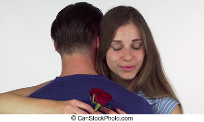 Beautiful woman smiling, holding red rose while embracing her boyfriend