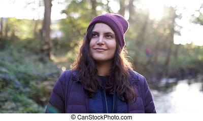 Beautiful brunette woman wearing knitted hat smiling next to a river in the forest. Happy woman in forest with river as background. Adventurous day in nature